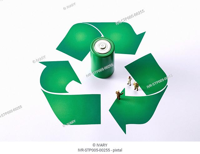 High angle view of recycling symbol with green battery and small figurines
