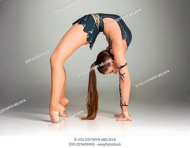 teenager doing gymnastics exercises on a gray background