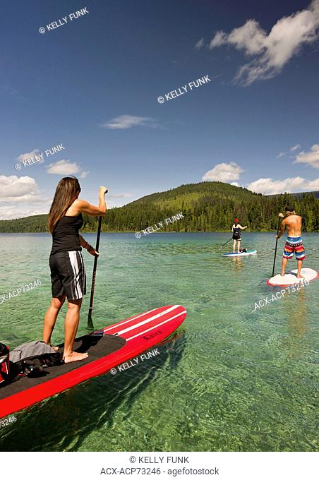 A group of paddle boarders make their way across the tropical like waters of Johnson Lake, North of Kamloops in the Thompson Okanagan region of British Columbia