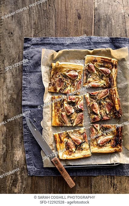 Sliced fig blue cheese and rosemary tart on baking tray with knife on grey background