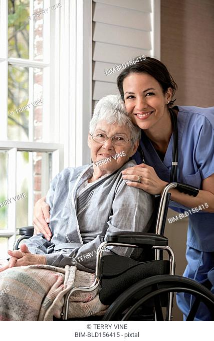 Nurse smiling with patient in wheelchair near window