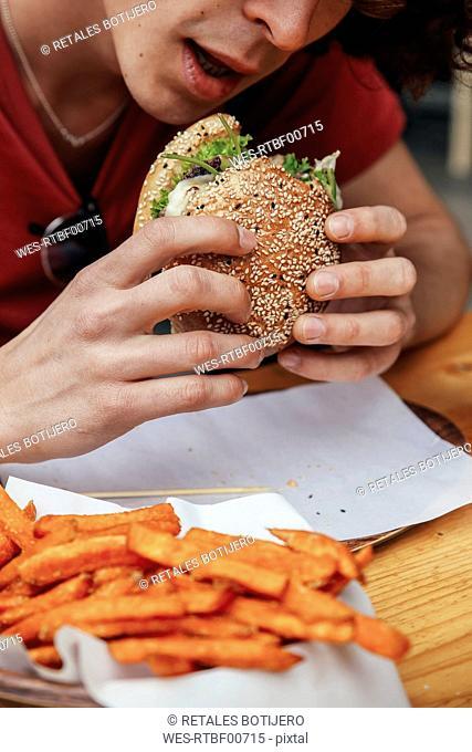 Young man eating vegan hamburger and sweet potato fries
