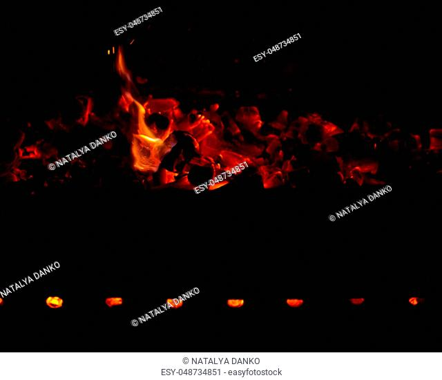 burning wooden logs in the fire at night, black background