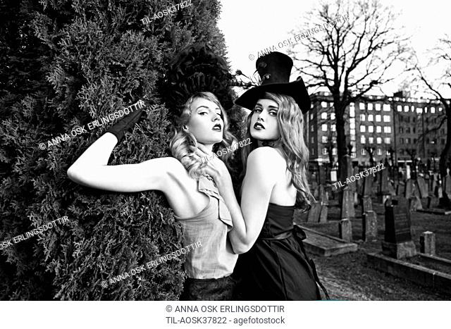 Two young adult females in graveyard