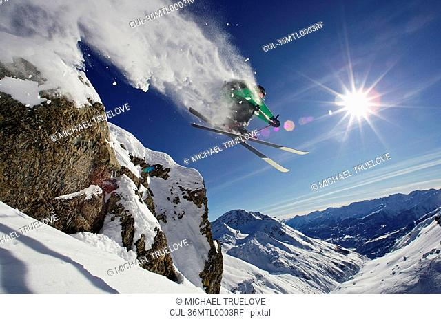 Skier in midair on snowy mountain