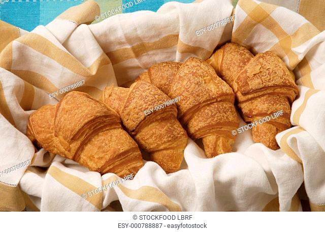 Four croisssants in bread basket