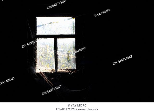 Old dirty window with cobweb around and darkness inside