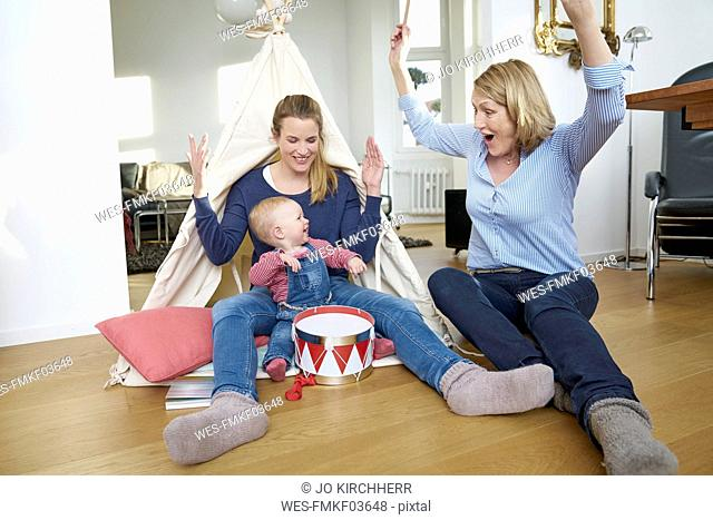 Happy grandmother, mother and baby girl playing at home