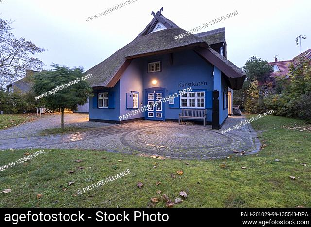 21 October 2020, Mecklenburg-Western Pomerania, Ahrenshoop: Warm light shines from the side windows of the Kunstkaten. The thatched building is one of the...