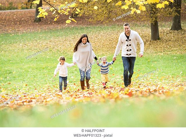 Happy family with two girls walking in autumn leaves