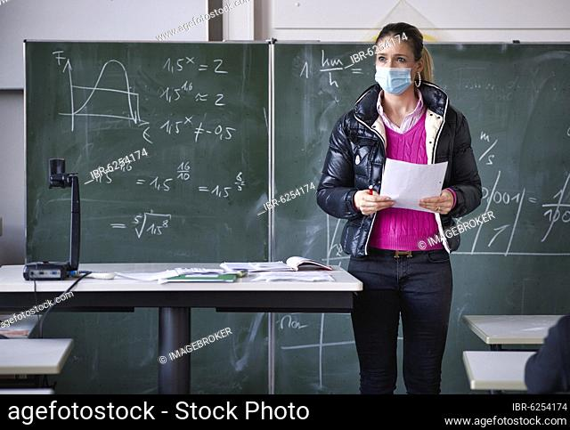 Teacher with winter jacket and face mask in classroom teaching, gestures, corona crisis, Stuttgart, Baden-Württemberg, Germany, Europe