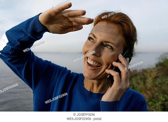 Germany, Hamburg, laughing woman on cell phone at Elbe shore