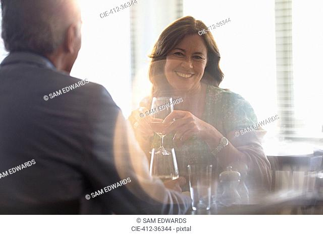 Smiling mature couple drinking wine, dining at restaurant table