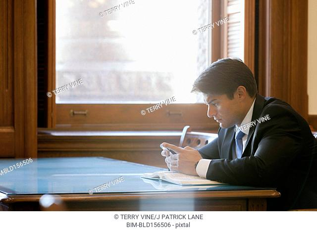 Hispanic businessman using cell phone in library