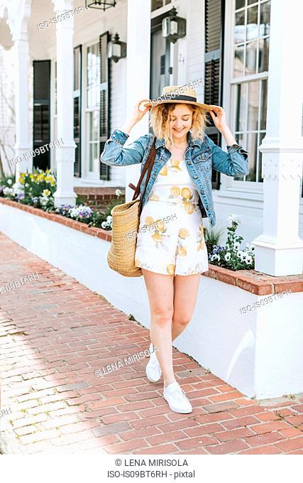 Young woman strolling on sidewalk wearing straw boater, Menemsha, Martha's Vineyard, Massachusetts, USA