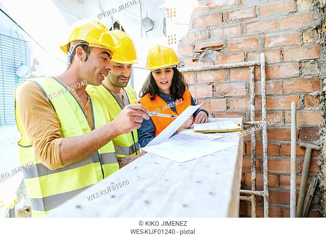 Woman and two construction workers talking on construction site