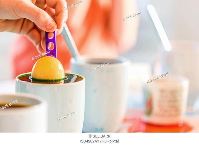 Close up of boy's hand dyeing egg in mug for Easter