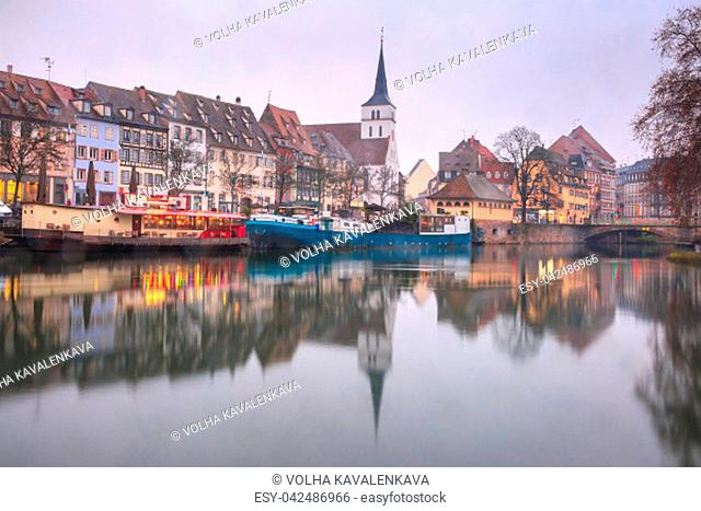 Picturesque quai des Pecheurs, Fisherman Wharf, and Protestant church of Saint Guillaume with mirror reflections in the river Ile during morning blue hour