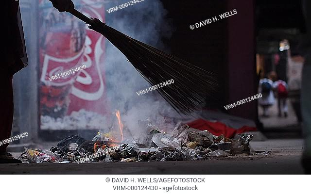 Sweeper gathering waste to burn at Haridwar, Uttarakhand, India