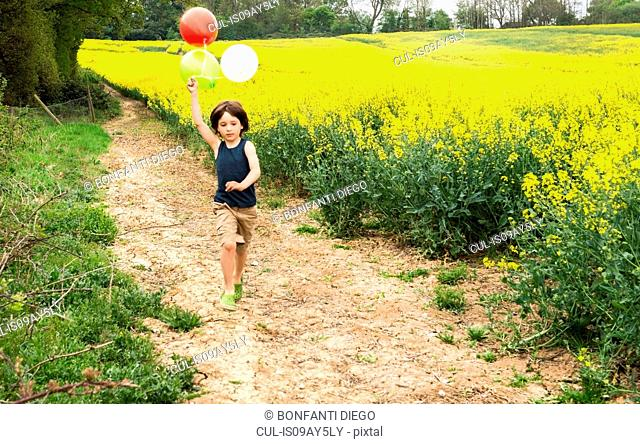 Boy running on yellow flower field track pulling balloons