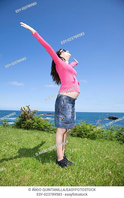open arms pregnant woman with pink jersey at Asturian coast