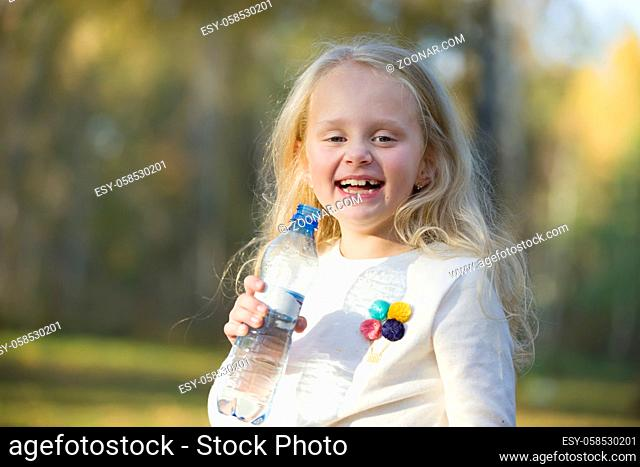 Joyful little girl child blonde drinks water from a bottle