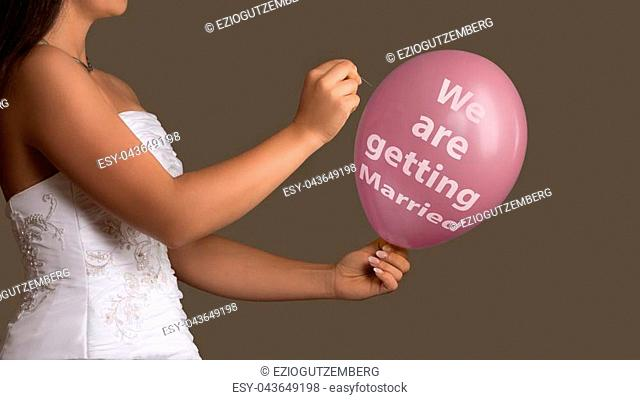 Young bride in wedding dress lets a Balloon with Text burst with a needle