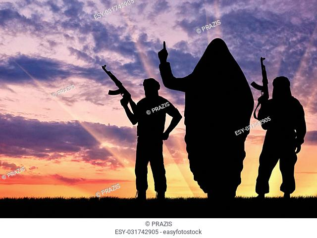 Concept of terrorism. Silhouette of three terrorists with weapons dictate their terms at sunset