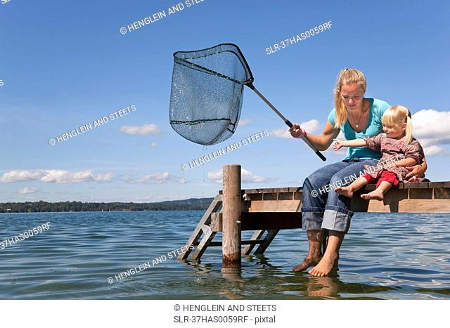 Mother and daughter fishing with net