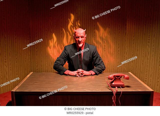 Businessman dressed as devil at desk