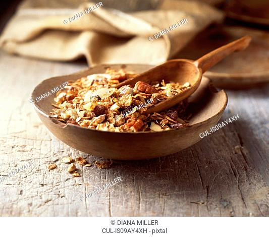 Food, muesli in wooden bowl, pecans, rolled oats, dried fruit, raisins, nuts, vintage