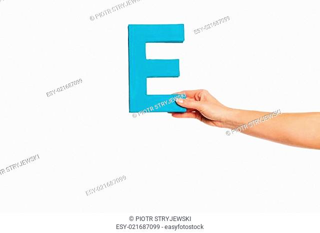 hand holding up the letter E from the right