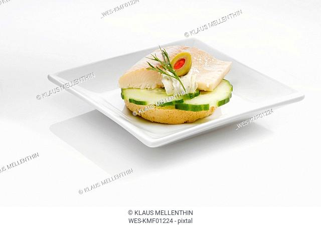 Sandwich with smoked trout fillet cucumber slices and olive