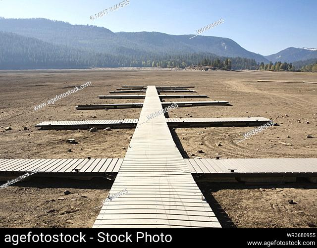 Planks laid out as walkways, jetties on flat dry desert soil, open space