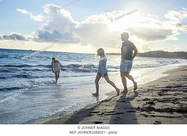 Father with daughters running into sea