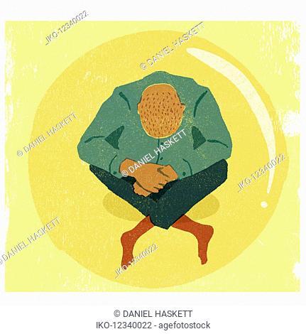 Overhead view of depressed man sitting crossed-legged on floor inside of bubble