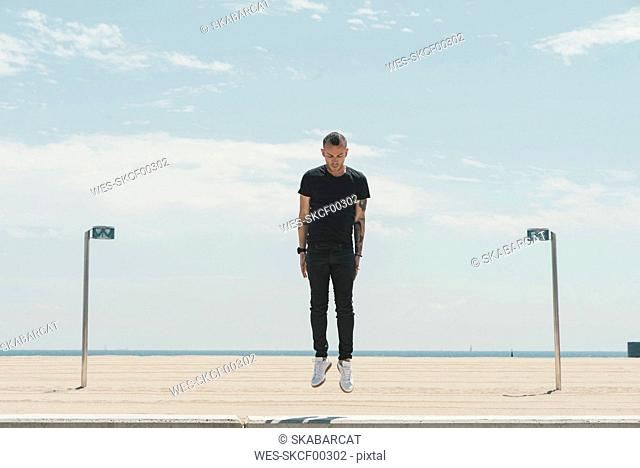 Young man with mohawk haircut and tattoos jumping in the air at the coast