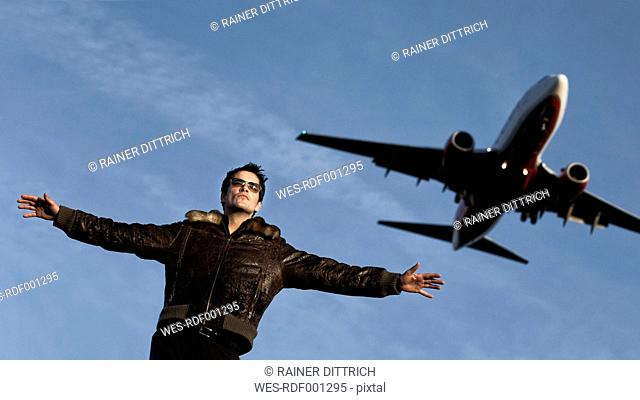 Germany, Mid adult man with airplane in background