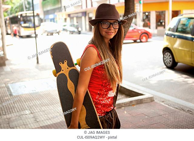 Portrait of young female hipster carrying skateboard, Rio De Janeiro, Brazil
