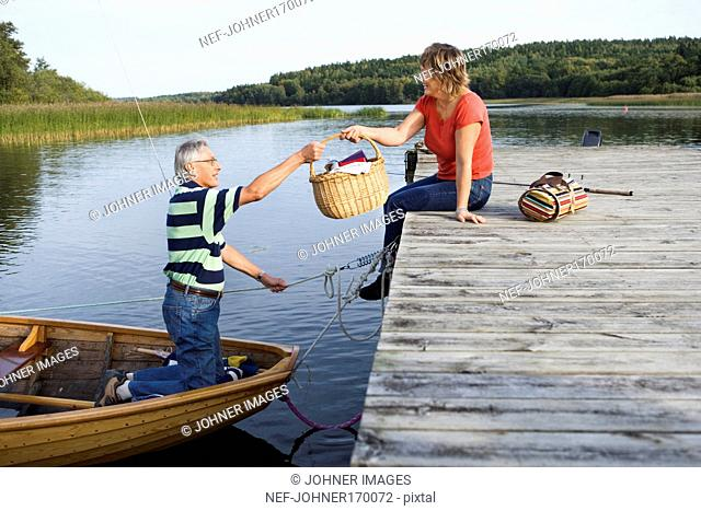 A couple on their way out for a picnic in a boat