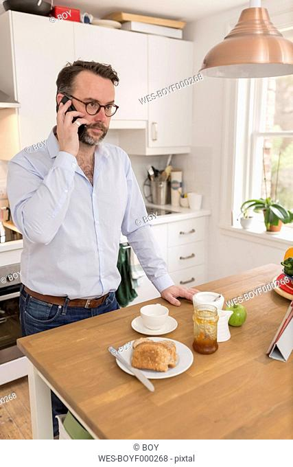 Man standing at breakfast table in the kitchen telephoning with smartphone