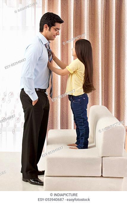Daughter adjusting father's tie