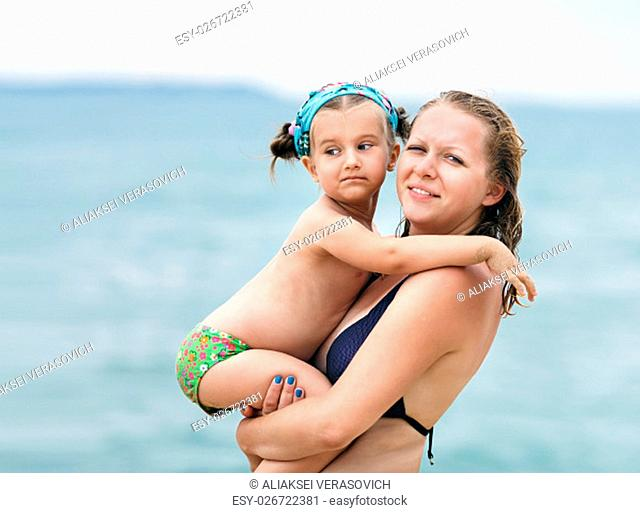 Hugging mother and daughter. Mom keeps little daughter in her arms on blurred background of the sea. Selective focus on the models