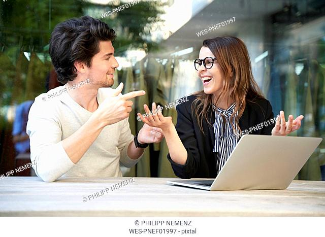 Businessman and happy businesswoman with laptop meeting in the city