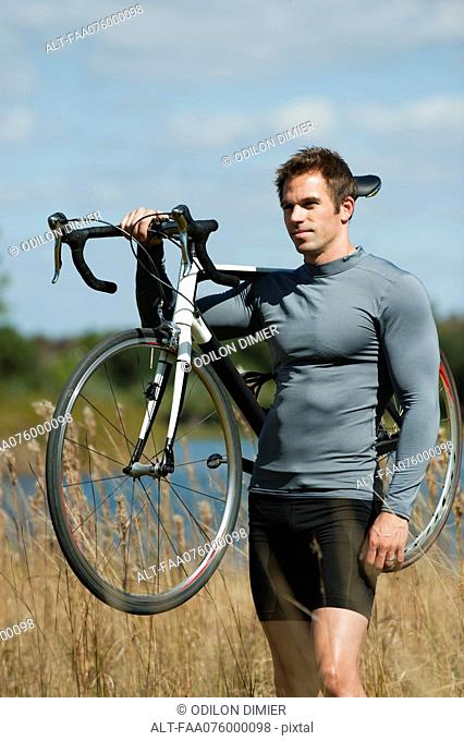 Man carrying bicycle on shoulder in nature, portrait