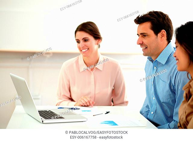 Portrait of attractive professional multi ethnic team looking at laptop while smiling and sitting on office desk