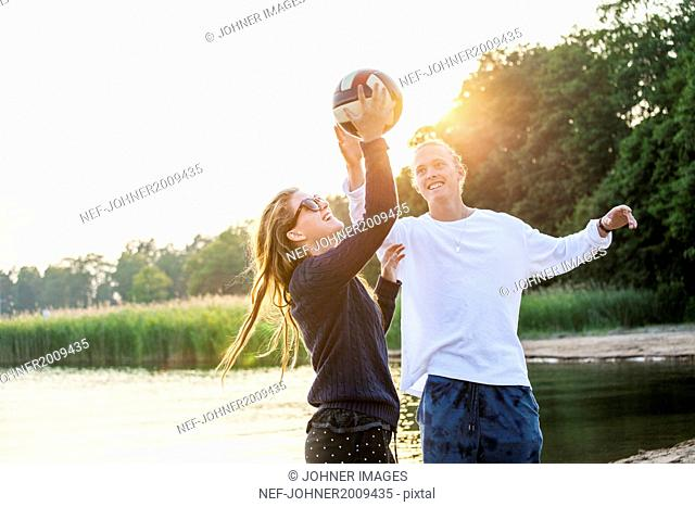 Young couple playing ball at water