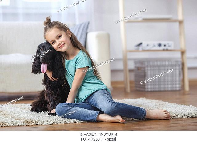 Portrait of cute girl embracing dog while sitting on rug at home