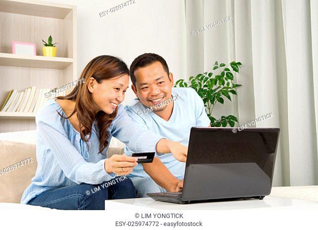 Asian couple using laptop to perform online shopping