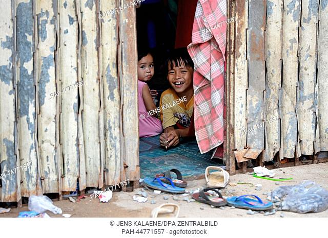 A boy and a girl look out of the door of their hut in the Chhba Anmpov Slum on the grounds of a Chinese graveyard in Phnom Penh, Cambodia, 10 December 2013